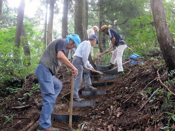セイバやスコップで溝を作り、そこへ階段を設置して固定するための杭をカケヤで打ち込めば一段完成。