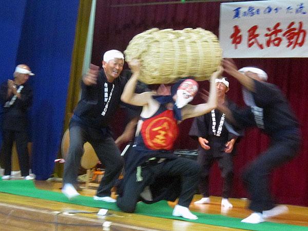 最初のにわか芸『米俵で力比べ』の一場面。俵を差し上げているのは私。