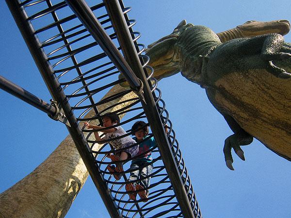 戦う恐竜の下を通る天空の回廊。三歳の孫は恐る恐る前進。(於:恐竜公園)