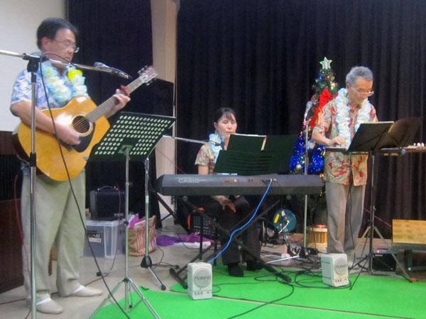 アロハシャツを着てレイを首から掛けて、3人でバンド演奏。