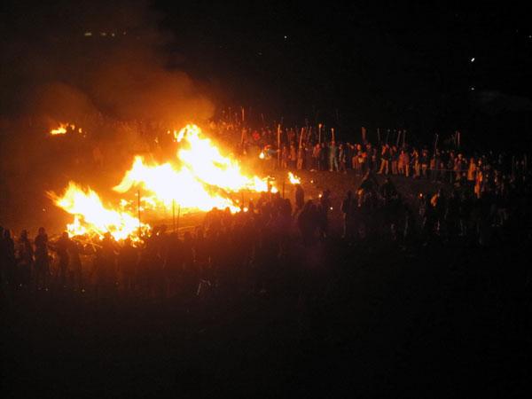 「福餅」を焼くためにどんど焼きに近づく人たち。