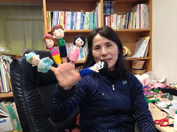 子育て支援センターで使う「お話指さん」の人形を示す家内。完成してホッと一息入れているところか。