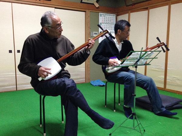 銭太鼓のエースが三味線にチャレンジ。二人ともギターを弾くので教え甲斐がある。