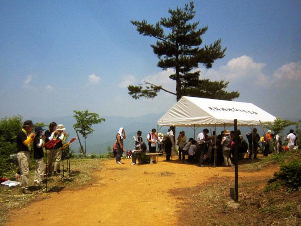 山頂へ到着したメンバーが豚汁やおにぎりの接待を受けて、昼食をとる中で演奏を続けた。