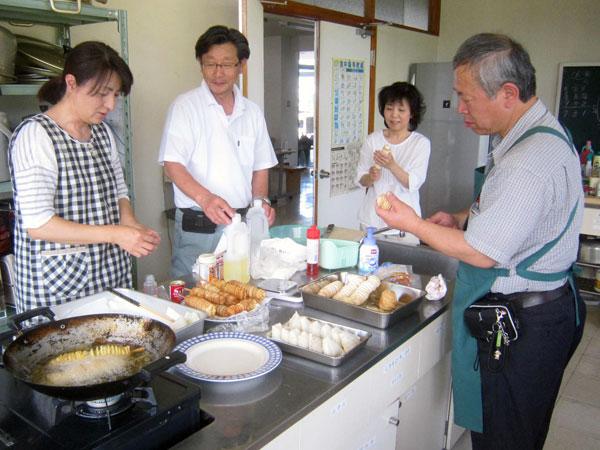 公民館の厨房で里芋を使った加工食品の研究をする『食品加工部会』のメンバー。