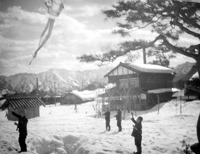 雪の中での凧揚げに興ずる昭和の子ども達(朝日印刷提供)