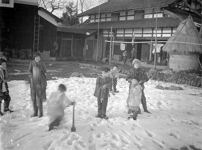 家の前で雪遊びをする子ども達。
