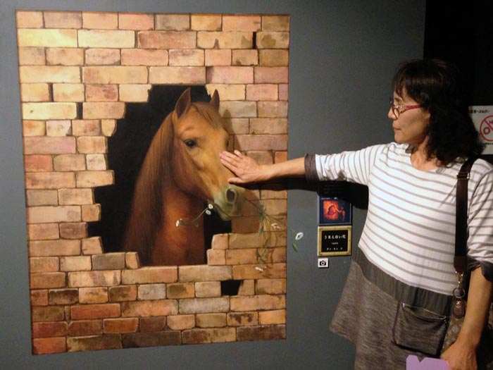 壁から顔を出している馬の顔をなでているようだが、実は壁に描かれた平面の絵の馬に触れているだけである。